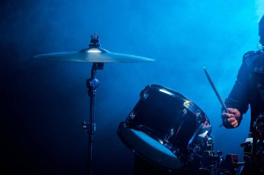 partial view of male musician playing drums during rock concert on stage with smoke and dramatic lighting