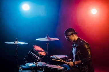 male musician in leather jacket playing drums during rock concert on stage with smoke and spotlights