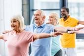 Fotografie glücklich multikulturellen senior Athleten synchrone Bewegung im Fitnessstudio