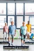 šťastná multikulturní senior sportovci synchronní, cvičení na platformách krok v tělocvičně