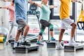Fotografie Teilansicht der senior Athleten synchrone Ausübung auf Schritt-Plattformen in Turnhalle
