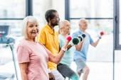 Selektivní fokus úsměvu senior sportovkyně a její přátelé cvičení s činkami ve sportovní hale