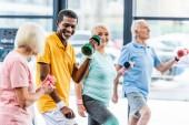 Ein lachender Afrikaner und seine Freunde machen im Fitnessstudio Übungen mit Kurzhanteln