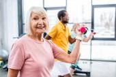 Selektiver Fokus der fröhlichen Seniorin und ihrer Freundinnen beim Training mit Hanteln im Fitnessstudio