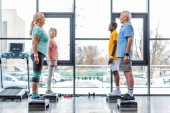 Fotografie side view of multicultural senior sportspeople standing on step platforms next to each other at gym