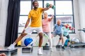Fotografie selektiven Fokus der senior multikulturellen Sportler synchrone Ausübung mit Hanteln auf Schritt-Plattformen in Turnhalle