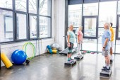 Fotografie senior sportspeople standing on step platforms next to each other at gym