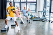 mnohonárodnostní senior sportovců synchronní, cvičení s činkami na platformách krok v tělocvičně