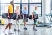 Fotografie multiethnische senior Sportler halten Schritt Plattformen in Turnhalle