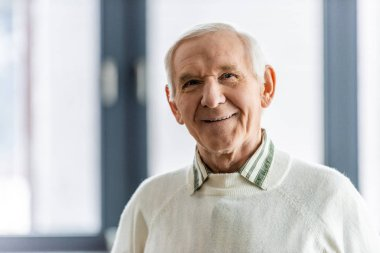 close up portrait of smiling senior man looking at camera