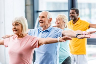 happy multicultural senior athletes synchronous doing exercise at gym