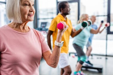 selective focus of senior sportswoman and her friends exercising with dumbbells at gym