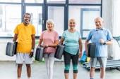 Fotografie multikulturelle senior Sportler halten Schritt Plattformen in Turnhalle