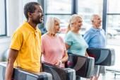 Selektivní fokus mnohonárodnostní senior sportovců drží krok platformy v tělocvičně