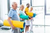 Glückliche Senioren mit Fitnessmatten in Sporthalle