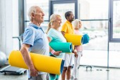 boční pohled multethnic senior sportovců drží fitness rohože v tělocvičně