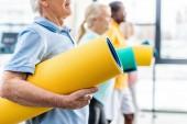 Teilansicht älterer Sportler mit Fitnessmatten bei Sportlern