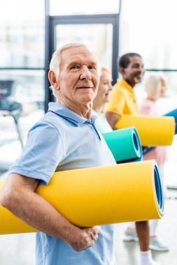 selective focus of senior sportsman holding fitness mat and his friends standing behind at gym