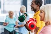 Selektiver Fokus eines reiferen interrassischen Paares bei Übungen mit Hanteln im Fitnessstudio