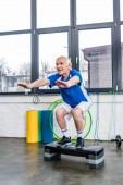 Seniorensportler macht Kniebeugen auf Trittplattform im Fitnessstudio