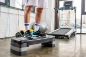 Fotografie zugeschnittenes Bild senior männlichen Athleten stehen auf Schritt-Plattform in Turnhalle