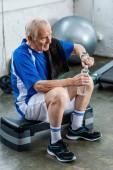 Fotografie Hochwinkelblick des Senior-Sportlers mit Handtuch öffnender Wasserflasche im Fitnessstudio