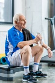 senior sportsman with towel and bottle of water resting at gym