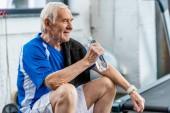 Lächelnder Senior-Sportler mit Handtuch und Wasserflasche im Fitnessstudio