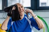 Veselý senior sportovec drží láhev vody a stírací hlavu ručník odpočívá v tělocvičně