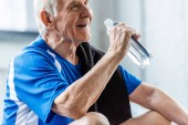 Selektiver Fokus des glücklichen Senior-Sportlers mit Handtuch und Wasserflasche im Fitnessstudio