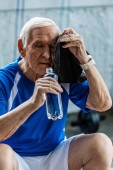tired senior sportsman holding bottle of water and wiping head by towel resting at gym