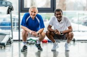 Lächelnde multiethnische Sportler, die in die Kamera schauen und in der Sporthalle sitzen