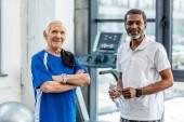 glückliche multikulturelle gestandene Sportler mit Smartwatches im Fitnessstudio