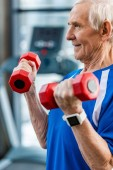 selective focus of senior sportsman with smartwatch doing exercise with dumbbells at gym