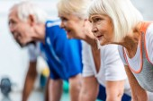 selective focus of senior sportswoman and her friends doing plank at gym