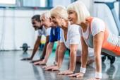 Fotografie Seitenansicht des Mutiethnic senior Sportler tun Plank in Sporthalle