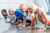 Veselá mutiethnic senior sportovci dělá prkno ve sportovní hale