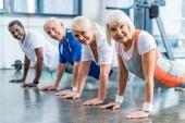 Fotografie Glückliche Senioren beim Planken im Fitnessstudio