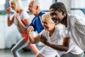 Happy americký sportovec synchronní, cvičení s přáteli ve sportovní hale