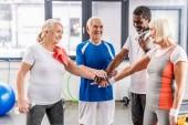 Fotografie lächelnd senior Multiculutral Freunde Zusammenstellung Hände in Sporthalle