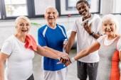 Fotografie Lachende multikulturelle Senioren legen in Sporthalle Hand an