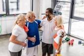 Blick aus der Vogelperspektive auf fröhliche multikulturelle Senioren, die sich im Fitnessstudio unterhalten und umarmen