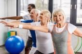Fotografie Glückliche Senioren beim Synchronturnen in Sporthalle