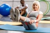 Fotografie Seniorin und ihr Mann trainieren auf Fitnessmatten im Fitnessstudio