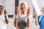 Fotografie Selektiver Fokus der älteren Sportlerin mit geschlossenen Augen, die im Fitnessstudio Sport macht