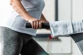 Teilbild einer Sportlerin, die auf Laufband in Sporthalle läuft