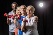 Senior-Sportlerin mit Hantel, die in die Kamera zeigt, während ihre Freunde hinten auf schwarz mit Scheinwerfer stehen