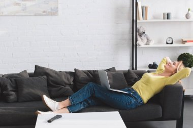 side view of happy relaxed woman lying with laptop on couch