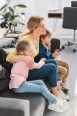 pohled z vysokého úhlu matku a děti s dálkovým ovládáním, seděl na pohovce a sledování televize