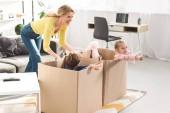 Fényképek játszó gyerekek karton dobozok otthon ül boldog anya